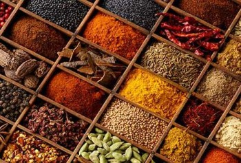 Variety of indian spices in a wooden tray.