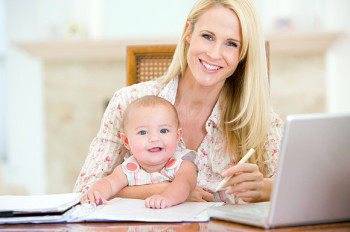 Mother and baby in dining room with laptop smiling